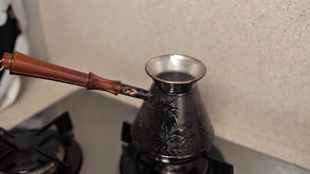 sporák : Woman brews coffee early in the morning in the kitchen on the gas stove. Turkish coffee, delicious aroma