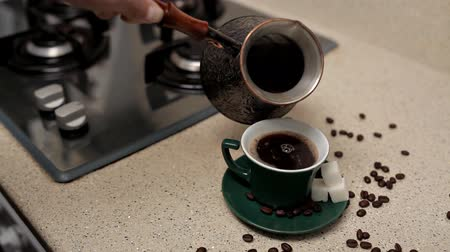 alışkanlık : Woman pouring hot aromatic coffee into cup at table, closeup. Lazy morning