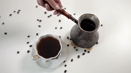 ébredés : A woman pouring hot aromatic coffee into a Cup at a white table on which coffee beans are scattered. Delicious coffee, morning, awakening