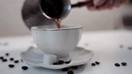 пробуждение : A woman pouring hot aromatic coffee into a Cup at a white table on which coffee beans are scattered. Delicious coffee, morning, awakening