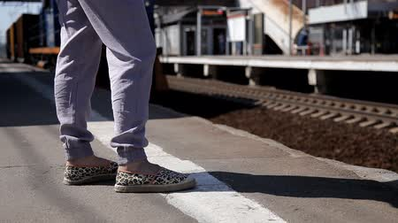 public transportation : womens legs on the railway platform waiting for the train. In the background a train is passing by