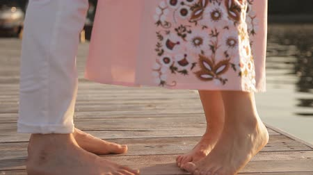 trousers : lovers on a wooden bridge at sunset. close-up of bare feet. Water in the background