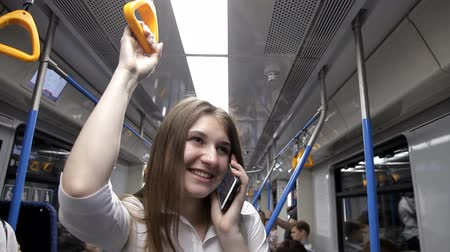 corrimão : a beautiful girl goes to the subway, holds the handrail and uses the phone