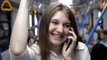 wozek dzieciecy : a beautiful girl goes to the subway, holds the handrail and uses the phone