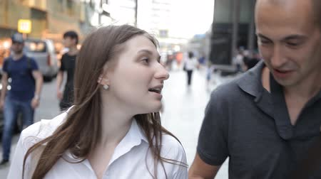 iluminado para trás : friends, a man and a woman, walking along a busy street in the city center and talking, smiling