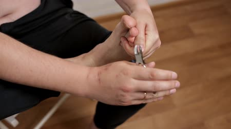 lakier do paznokci : A man cuts long toenails with scissors, tweezers. Bathroom