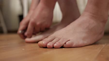 short clip : Man neatly cuts his toenails close-up. A man makes himself a pedicure at home on the floor