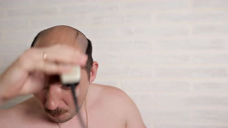 beard trim : funny guy with a mustache shaves his head with an electric razor in the bathroom and dances Stock Footage