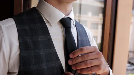 gravata : Young stylish man in a white shirt is standing, tying a tie. Wedding preparations