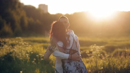 whirling : Young man and woman strolling in a meadow at sunset in summer. Romance. Summer love togetherness joy romantic memories forever together concept Stock Footage