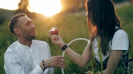 hazugság : A young man and woman are sitting on a green meadow and eating an apple. Romance, love