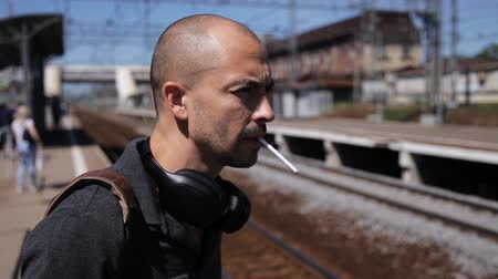 impatience : Charismatic man on the platform of the railway station lights a cigarette and waits for the train. Man in headphones smokes on the platform on a sunny day. Stock Footage
