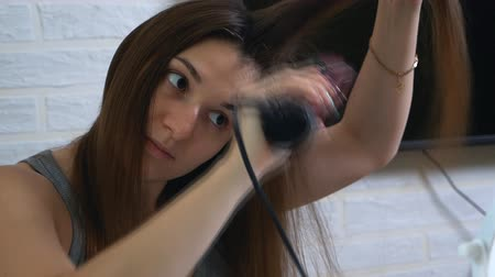 gloss : Young pretty woman combing her hair in front of the mirror Stock Footage