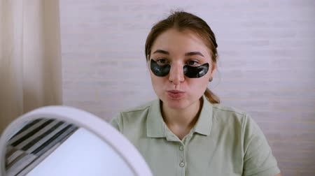 eye mask : The girl uses black patches under her eyes, smiling, sitting opposite the mirror. Healthy lifestyle, youth, facial