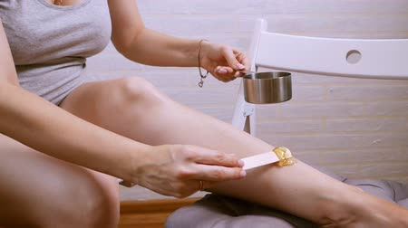aplikatör : beauty, depilation, epilation, hair removal and people concept - beautiful woman with applicator applying depilatory wax to her leg