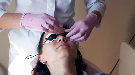 depilation laser : Preparation for laser hair removal. Girl with glasses before laser hair removal Stock Footage