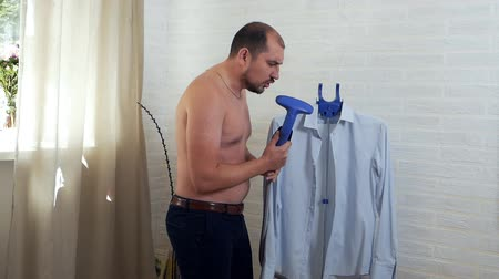 ütüleme : The man is having fun, stroking his shirt and humming at home