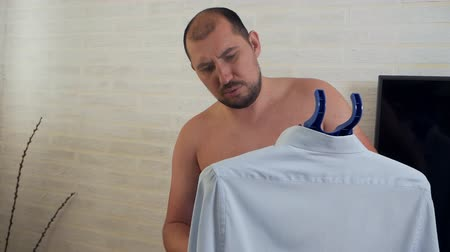 žehlení : Bald man using steam system for ironing clothes, steaming shirt at home