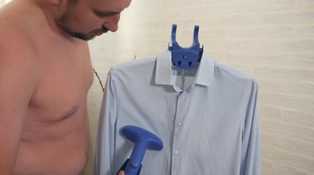 гладильный : A man strokes, steam, boil a blue shirt at home