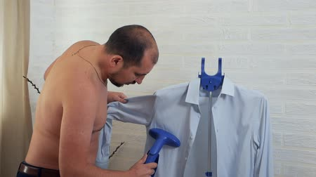 crinkle : Bald man using steam system for ironing clothes, steaming shirt at home