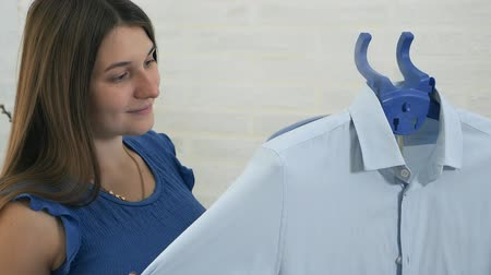 žehlení : The young woman smiles and uses steam to stroke the mans shirt. The process of steaming clothes with steam