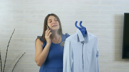 žehlení : A young woman speaks on the phone and uses steam to stroke the mans shirt. The process of steaming clothes steam. Blue details Dostupné videozáznamy