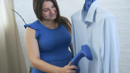 parník : A young pregnant woman touches her stomach and uses steam to stroke the mans shirt. The process of steaming clothes steam. Blue details Dostupné videozáznamy