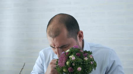 soulager : Allergy, pollen, a young man holds a bouquet of flowers and sneezes
