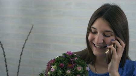 発見 : A young woman found a bouquet of flowers at home. Happy excited girl calls a guy