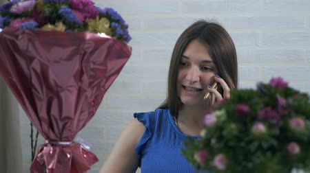 chrysanthemum : A young girl at home puts bouquets of flowers in a cart with water and speaks on the phone