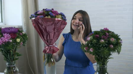 chryzantema : A young girl at home puts bouquets of flowers in a cart with water