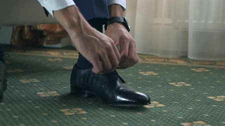 носок : Groom puts on shoes on wedding day