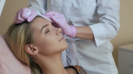 forro : Beautician wipes the face with a cotton pad to the client, preparing for the procedure Stock Footage