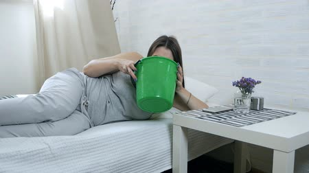 vomit : Morning sickness. Young pregnant woman lies on a couch and vomits in a bucket. Pregnancy intoxication