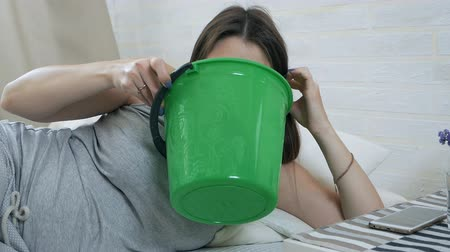 donna in gravidanza : Morning sickness. Young pregnant woman lies on a couch and vomits in a bucket. Pregnancy intoxication