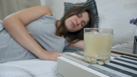 hangover : A pregnant girl throws an effervescent pill into a glass. Stock Footage