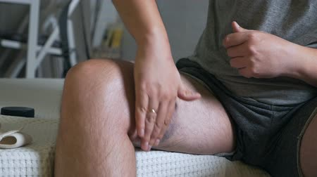 bruising : A young bald man with ointment smears a sore leg with a bruise. Violet leg. Athletic foot damage. Stock Footage