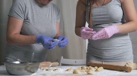 пельмени : Cooking modeling dumplings at home. Mother and pregnant daughtermake dumplings