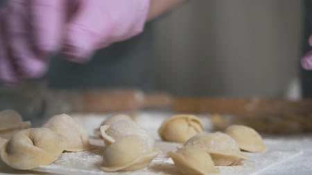 pelmeni : Cooking dumplings. Dumplings on the table, hands in gloves throw flour on dumplings Stock Footage
