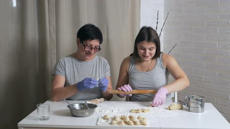 pelmeni : A pregnant girl and her mother sit at a table in the home kitchen and prepare dumplings with minced meat for lunch, roll out the dough with a rolling pin