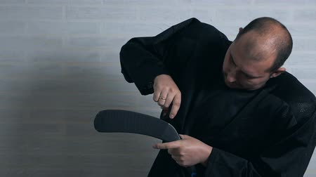 handling : A hockey player in black uniform wraps a hockey stick with a special black ribbon. Hockey equipment Stock Footage