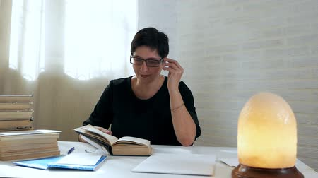 книжный шкаф : A librarian checks books after readers. Woman leafing through books in the library against the background of a dim lamp. The concept of knowledge. Reading, library, knowledge Стоковые видеозаписи