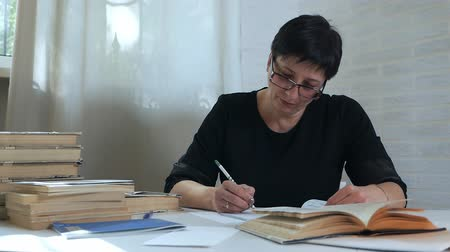 exercício : A woman in glasses with a pencil in her hand takes notes on paper, thinks and ponders, composes poems, poems. Creativity of the poetess. Telephone conversation with publisher