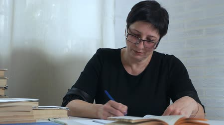 exercício : A woman in glasses with a pencil in her hand takes notes on paper, thinks and ponders, composes a poem, a verse. Creativity of the poetess