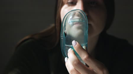 respirator : Use a nebulizer and inhaler for treatment. Young woman inhaling inhaler through a mask
