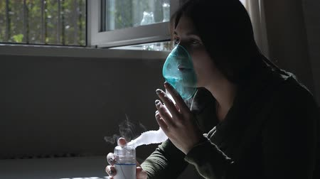 respirator : Use nebulizer and inhaler for the treatment. Young woman inhaling through inhaler mask. Side view
