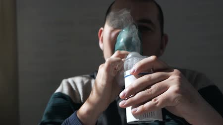 tosse : Young man holding a mask from an inhaler at home. Treats inflammation of the airways via nebulizer. Preventing asthma and cough
