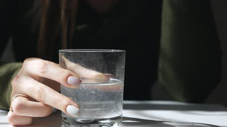 efervescente : The effervescent tablet for pain in a glass dissolves. Aspirin tablet in a glass. Hands of a girl in Huron are planning a glass with aspirin