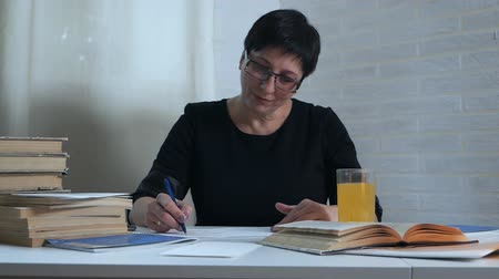 exercício : A woman in a black dress sits at a table on a white background and takes notes on paper, drinks a glass of water and vitamins for brain activity. Poetess, poet, creativity, books Vídeos