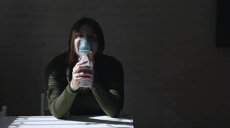 inhalacja : Use a nebulizer and inhaler for treatment. Young woman sitting at a table inhaling inhaler through a mask on a dark background